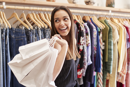 Female Customer Standing By Racks Of Clothes In Independent Fashion Store Holding Bags