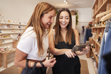 Two Female Friends Looking At Mobile Phone As They Shop In Independent Fashion Store