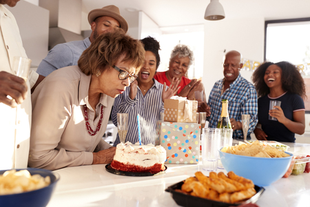 Middle aged black woman cutting cake during a three generation family birthday celebration,close up