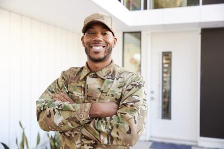 Soldado en camuflaje de pie fuera de casa moderna con los brazos cruzados sonriendo a la cámara, cerrar