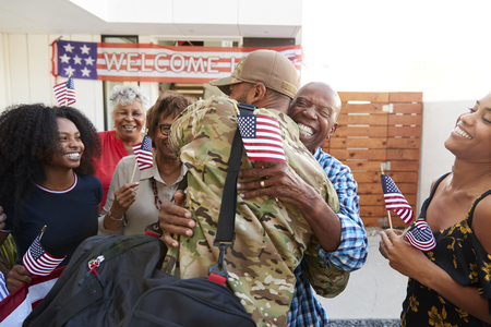 Millennial black soldier returning home to his family, embracing grandfather, back view