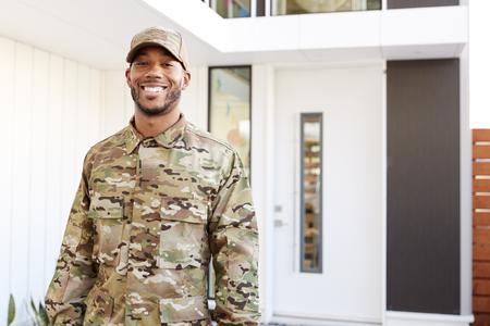 Soldat millénaire en uniforme de camouflage à l'extérieur d'une maison moderne souriant à la caméra, gros plan Banque d'images