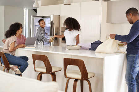 Black family in their kitchen, unpacking groceries and putting them away together
