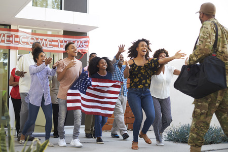 Three generation black family running out of house to welcome soldier returning home, low angle view Stock Photo