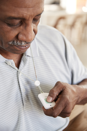 Senior black man pushing an assistance alarm which he's wearing around his neck, close up, vertical