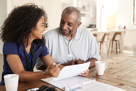 Happy female healthcare worker sitting at table smiling with a senior man during a home health visit