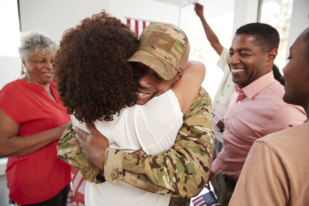 Millennial black soldier returning home embracing family members,close up Imagens