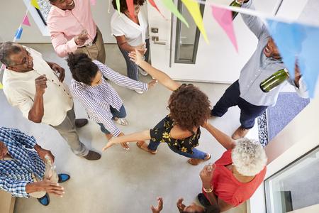 Famille de trois générations organisant une fête surprise accueillant des invités à la porte d'entrée, vue aérienne