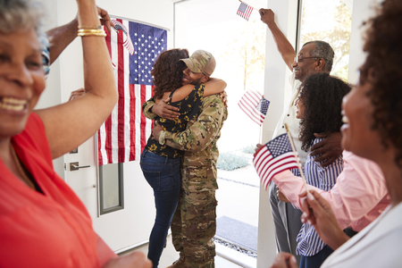 Millennial woman and family welcoming young black male soldier home, embracing in doorway, close up Stock Photo