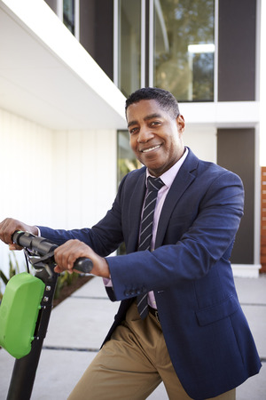 Smartly dressed middle aged black man standing on electric scooter in front of his house, close up