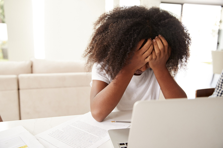 Depressed young teenage black girl with head in hands using laptop computer at home, close up