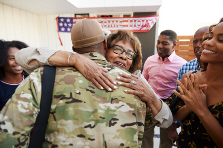 Millennial black soldier returning home to his family, embracing grandmother, back view Stock Photo