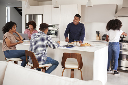 Happy black family talking and preparing a family meal together in their kitchen Stockfoto