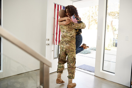 Returning millennial black soldier lifting his wife off her feet in the doorway of their home Stockfoto