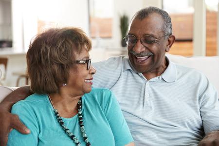 Älteres schwarzes Paar, das zu Hause sitzt, sich anlächelt, Nahaufnahme Standard-Bild