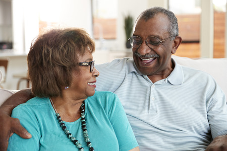 Senior black couple sitting at home, smiling at each other, close up