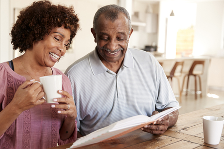 Middle aged black woman and her dad looking through photo album together at home, close up Foto de archivo - 119506782