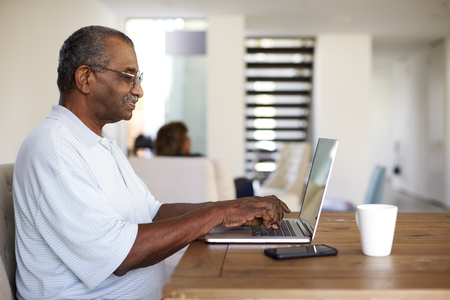 Senior black man sitting at the table using a laptop computer at home, side view