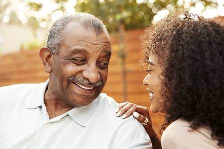Senior black man and his adult granddaughter laughing outdoors, close up