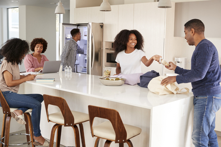 Black family unpacking groceries and spending time in their kitchen together