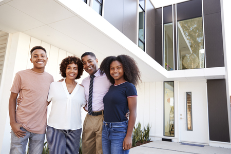 Black family stand looking to camera in front of their modern home,close up