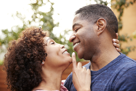 Happy middle aged black couple embracing outdoors, side view,close up