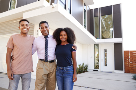 Black middle aged single mother and her kids standing in front of their modern home,close up