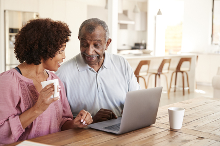 Senior black man and his middle aged daughter using a laptop together at home, close up Stock Photo - 119507551