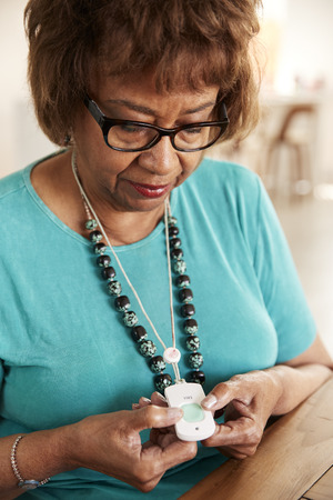 Senior mixed race woman pushing an assistance alarm which she's wearing around her neck, close up