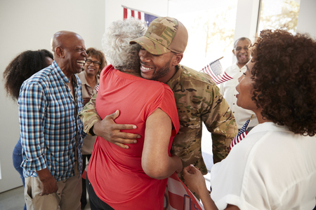 Millennial black soldier returning home to family embracing his grandmother,close up