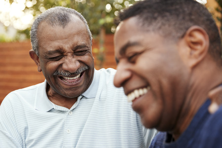 Senior black man and his adult son laughing together outdoors, close up