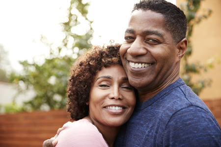 Happy middle aged black couple embracing smile to camera, close up