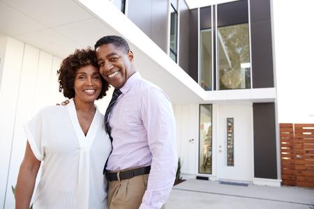 Zwart stel van middelbare leeftijd staat buiten en kijkt naar de camera voor hun moderne huis, close-up