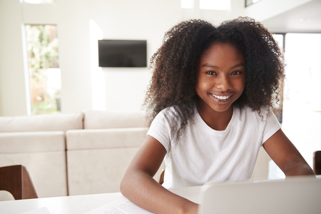 Happy young teenage black girl using laptop computer at home, close up 版權商用圖片