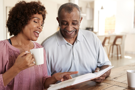 Senior black man and his middle aged daughter looking through photo album together at home, close up Foto de archivo - 119507680