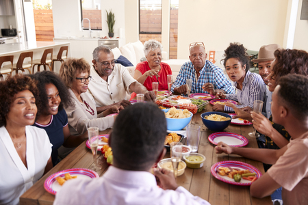 Three generation black family sitting at dinner table celebrating together,close up