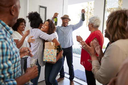 Millennial black couple arriving at a family party with gifts and champagne, close up