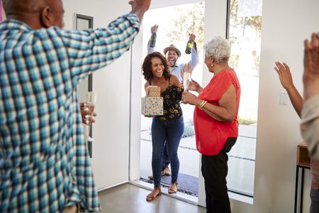Millennial black couple are greeted as they arrive at a family party with gifts and champagne