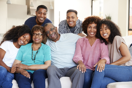 Multi generation black family sitting at home smiling to camera Standard-Bild