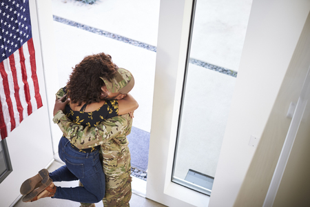 Returning millennial black soldier lifting his wife off her feet in the doorway of their home, elevated view Stok Fotoğraf