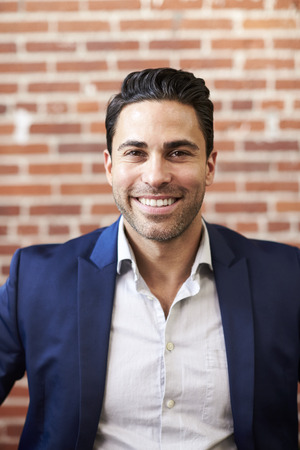 Portrait Of Smiling Mature Businessman Standing Against Brick Wall In Modern Office Фото со стока