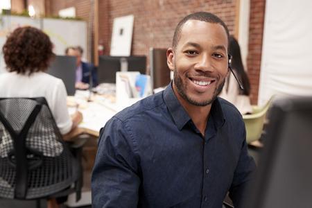 Portrait Of Male Customer Services Agent Working At Desk In Call Center Archivio Fotografico