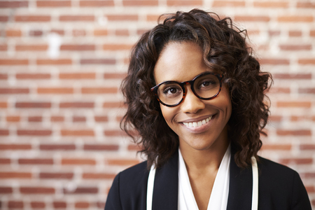Portrait Of Smiling Businesswoman Wearing Glasses Standing Against Brick Wall In Modern Office