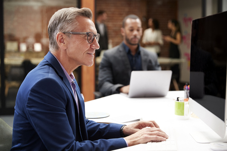 Mature Businessman Working At Desk On Computer In Open Plan Office With Colleagues In Background