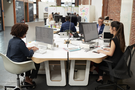 Business Team Working At Desks In Modern Open Plan Office Stock Photo