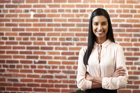Portrait Of Smiling Young Businesswoman Standing Against Brick Wall In Modern Office