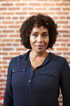Portrait Of Smiling Mature Businesswoman Standing Against Brick Wall In Modern Office