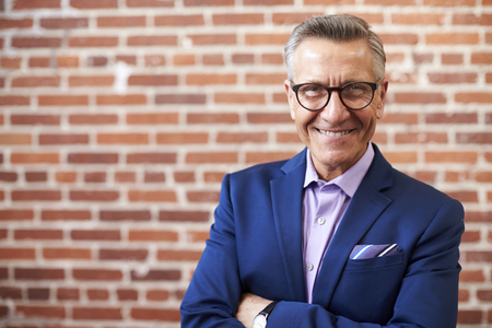 Portrait Of Smiling Mature Businessman Standing Against Brick Wall In Modern Office Stock Photo