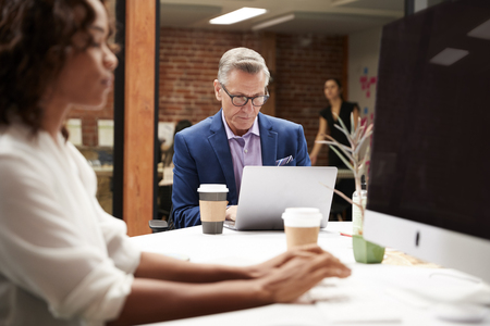 Mature Businessman Working At Table On Laptop In Open Plan Office With Colleagues In Background