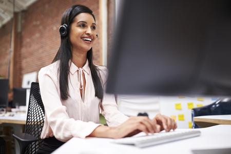 Vrouwelijke klantenservicemedewerker die aan de balie in het callcenter werkt Stockfoto